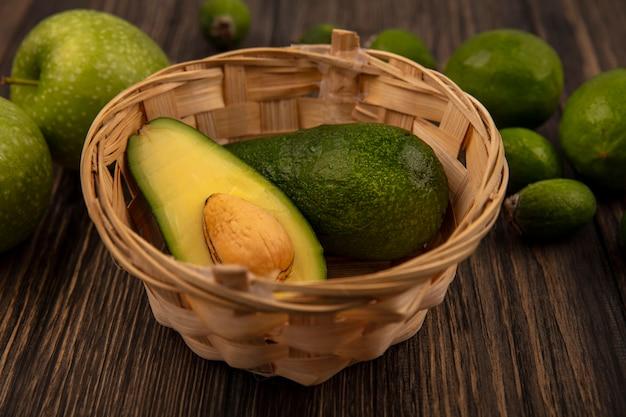 Bovenaanzicht van verse avocado's op een emmer met groene appels limoenen en feijoas geïsoleerd op een houten muur
