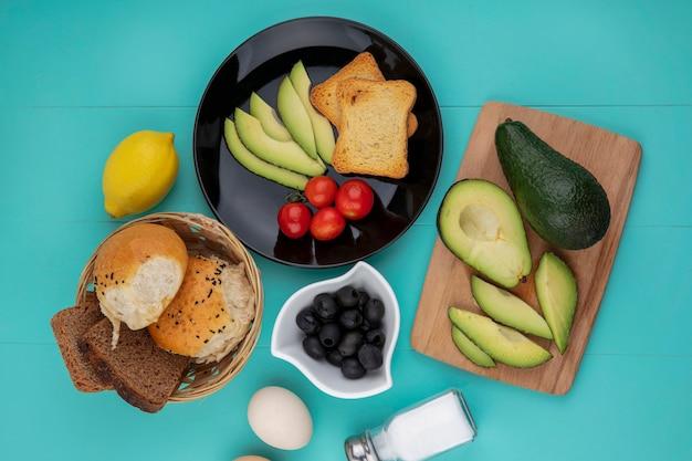 Bovenaanzicht van verse avocado's op houten keukenbord met een avocado plakjes tomaten in een zwarte plaat met een emmer brood op blauw