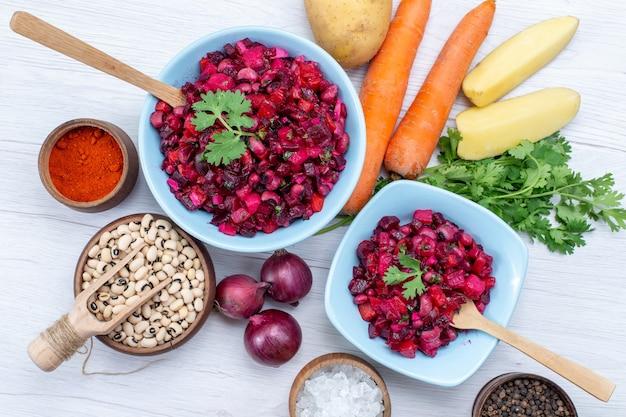 Bovenaanzicht van verse bietensalade met gesneden groenten binnen blauwe platen met ingrediënten op licht bureau, groente salade voedsel maaltijd gezondheid snack