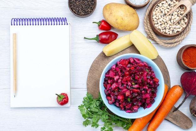 Bovenaanzicht van verse bietensalade met gesneden groenten samen met rauwe bonen wortelen aardappelen kladblok op licht bureau, voedsel maaltijd groente verse salade