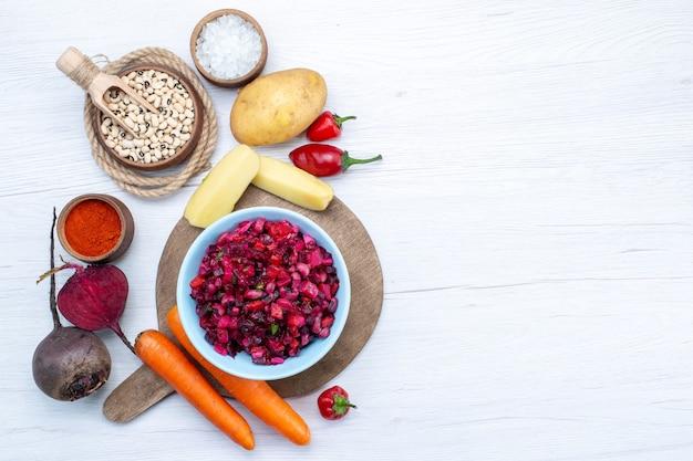 Bovenaanzicht van verse bietensalade met gesneden groenten samen met rauwe bonen wortelen aardappelen op licht bureau, voedsel maaltijd groente verse salade