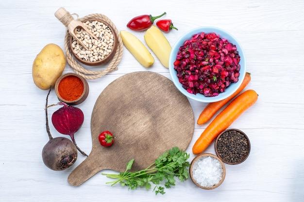 Bovenaanzicht van verse bietensalade met gesneden groenten samen met rauwe bonen wortelen aardappelen op wit bureau, voedsel maaltijd groente verse salade