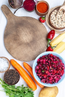Bovenaanzicht van verse bietensalade met gesneden groenten samen met rauwe bonen wortelen aardappelen op wit bureau, voedsel maaltijd plantaardige salade