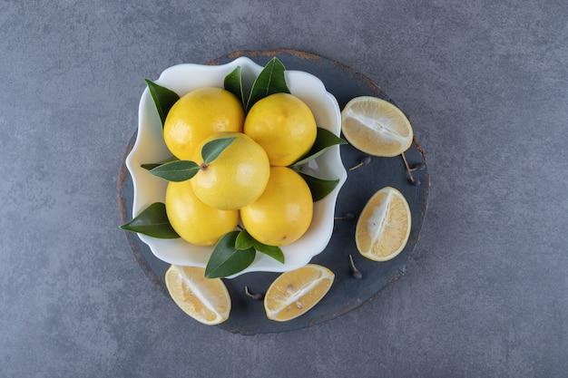 Bovenaanzicht van verse biologische citroenen en plakjes over houten bord.