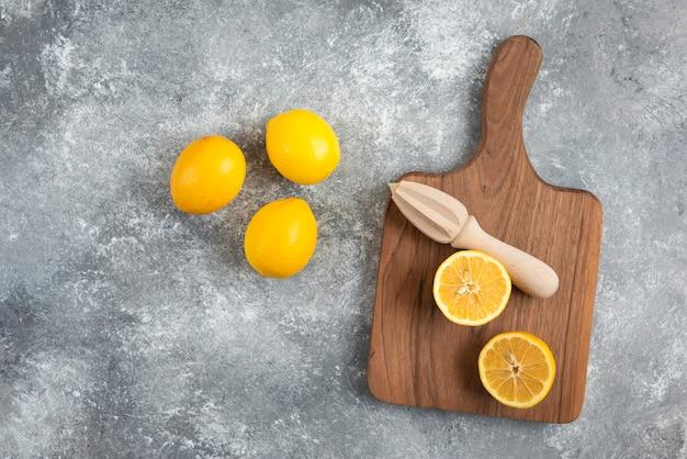 Bovenaanzicht van verse biologische citroenen op houten snijplank en op de grond.