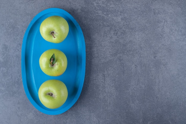 Bovenaanzicht van verse biologische groene appels op blauwe houten bord.