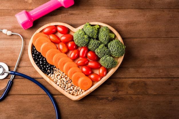 Bovenaanzicht van verse biologische groenten en fruit in hartplaat hout dokter stethoscoop en halter