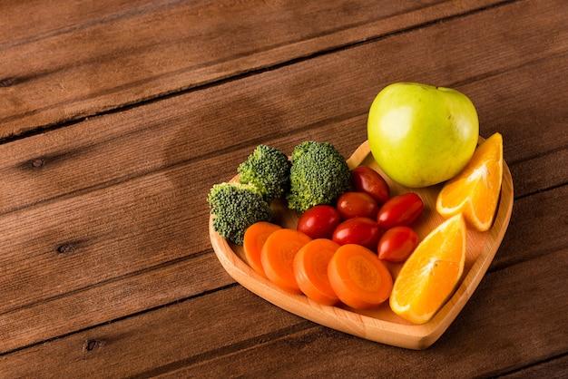 Bovenaanzicht van verse biologische groenten en fruit in hartplaathout