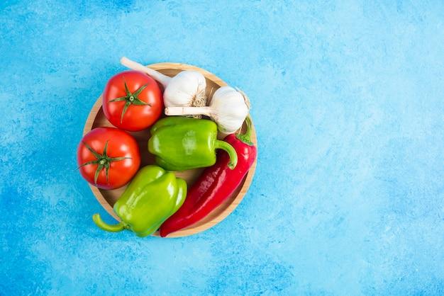 Bovenaanzicht van verse biologische groenten op een houten bord.
