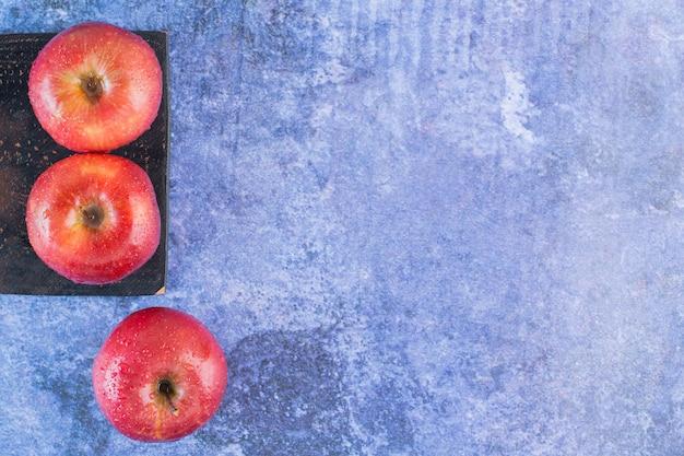 Bovenaanzicht van verse biologische rode appels op een houten bord over blauw.