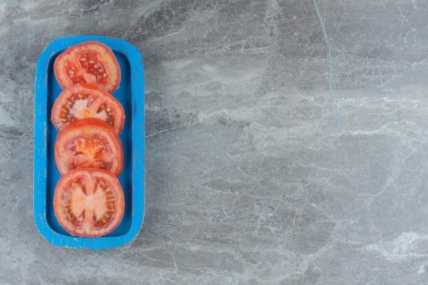 Bovenaanzicht van verse biologische tomatenschijfjes op blauwe houten plank