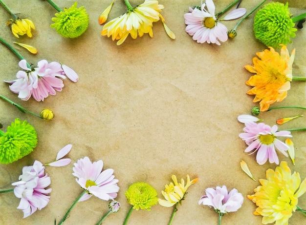 Bovenaanzicht van verse bloemen op kraftpapier in plat lag samenstelling. vintage achtergrond