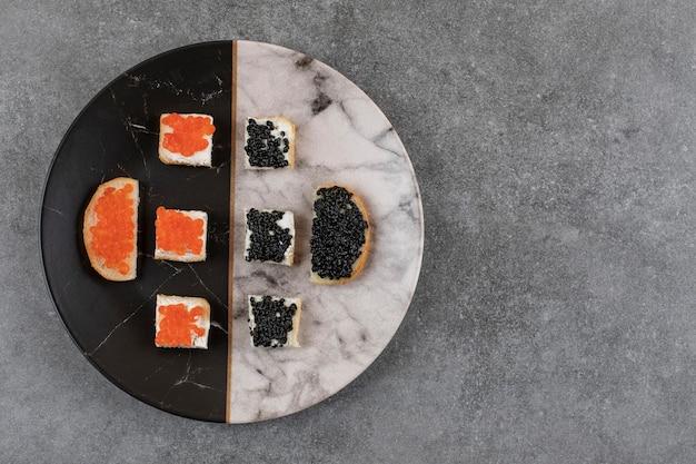 Bovenaanzicht van verse broodjes met kaviaar op kleurrijke plaat