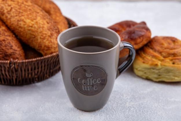Bovenaanzicht van verse broodjes op een emmer met een kopje thee op een witte achtergrond