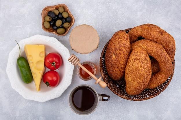 Bovenaanzicht van verse broodjes op een emmer met kaas, tomaat en komkommer op een kom op een witte achtergrond
