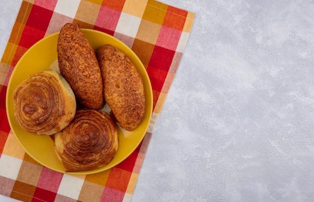 Bovenaanzicht van verse broodjes op een gele plaat op een gecontroleerde doek op een witte achtergrond met kopie ruimte