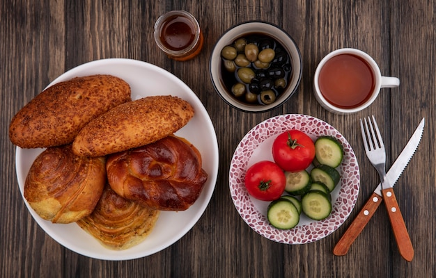 Bovenaanzicht van verse broodjes op een witte plaat met groenten met olijven op een kom op een houten achtergrond