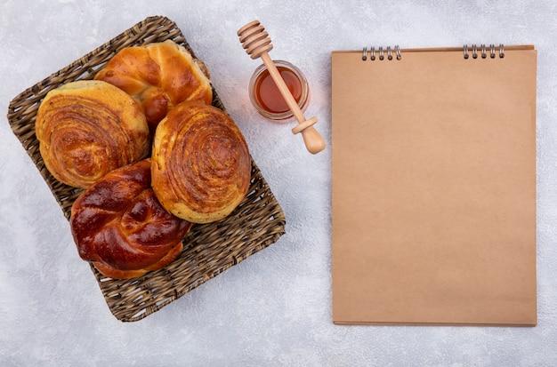 Bovenaanzicht van verse broodjes op rieten dienblad met honing en honinglepel op een witte achtergrond met kopie ruimte