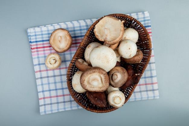 Bovenaanzicht van verse champignons in een rieten mand op geruite servet op lichtblauwe ondergrond