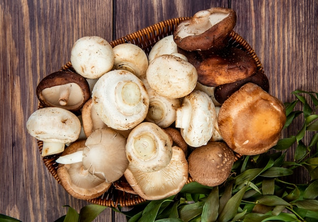 Bovenaanzicht van verse champignons in een rieten mand op rustiek hout