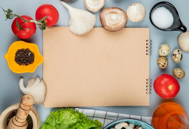 Bovenaanzicht van verse champignons met tomaten, zwarte peperkorrels, kwarteleitjes en zout, gerangschikt rond een schetsboek op lichtblauw