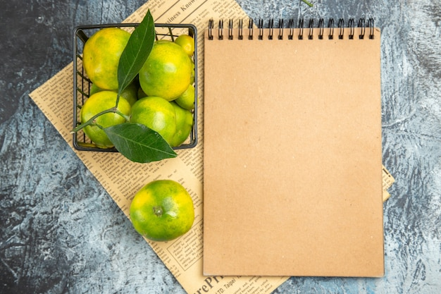 Bovenaanzicht van verse citroenen binnen en buiten mand op krant op grijze achtergrond