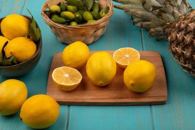 Bovenaanzicht van verse citroenen geïsoleerd op een houten keukenbord met citroenen op een kom met ananas geïsoleerd op een blauwe houten muur