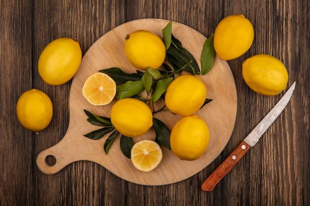 Bovenaanzicht van verse citroenen geïsoleerd op een houten keukenbord met mes op een houten muur