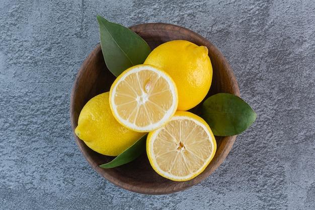 Bovenaanzicht van verse citroenen in houten kom over grijs.