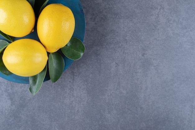 Bovenaanzicht van verse citroenen op blauw bord over grijze achtergrond.