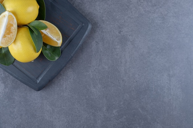 Bovenaanzicht van verse citroenen op grijs houten bord.