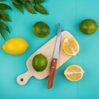 Bovenaanzicht van verse citroenen op houten keukenbord met mes en bladeren op blauw