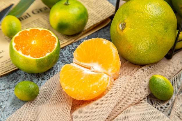 Bovenaanzicht van verse citrusvruchten gesneden in halve vormen en mes op krant op grijze achtergrond