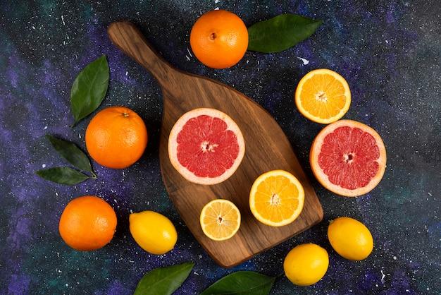 Bovenaanzicht van verse citrusvruchten met bladeren in houten plank.