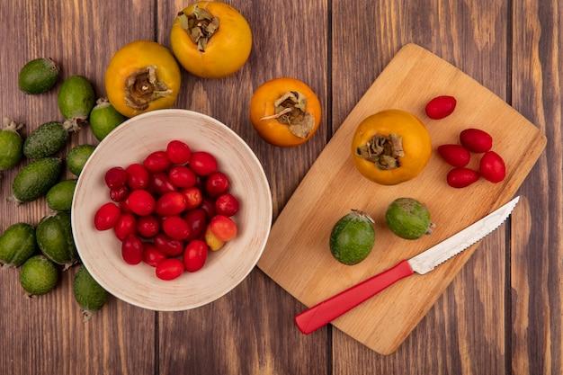 Bovenaanzicht van verse cornelian kersen op een kom met kaki en feijoas op een houten keukenplank met mes op een houten oppervlak