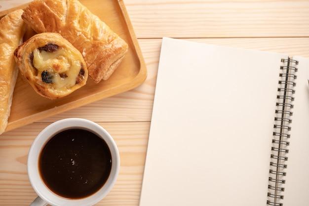 Bovenaanzicht van verse desserts en taarten geplaatst op houten laden geplaatst naast een leeg notitieboekje en witte koffiemokken.