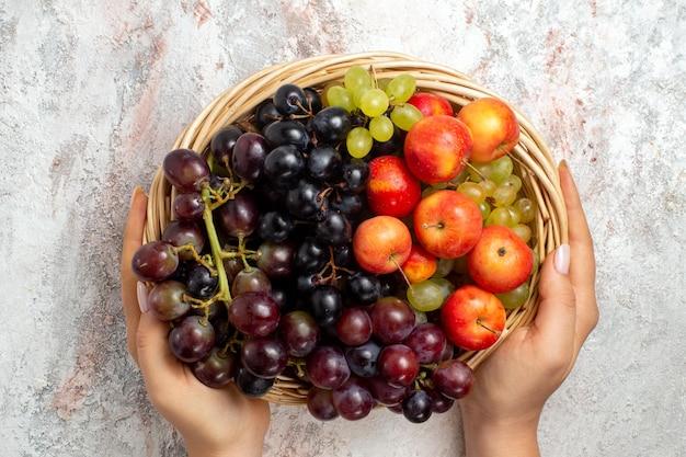 Bovenaanzicht van verse druiven in mand op wit oppervlak