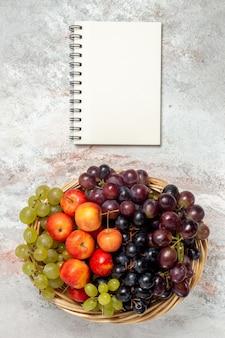 Bovenaanzicht van verse druiven met pruimen op witte ondergrond
