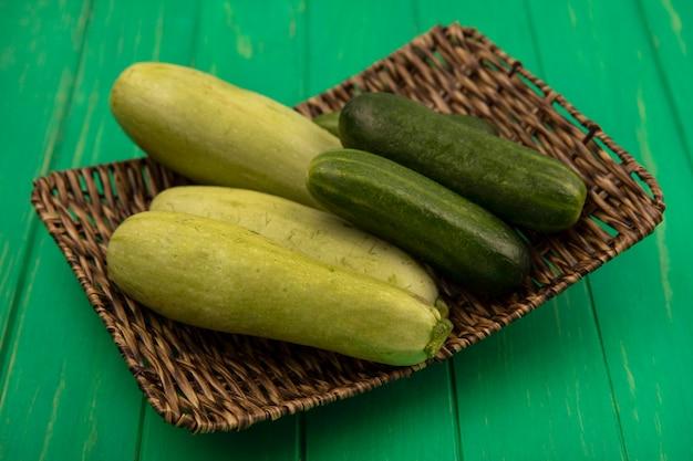 Bovenaanzicht van verse en gezonde groenten zoals komkommers en courgettes op een rieten dienblad op een groene houten muur