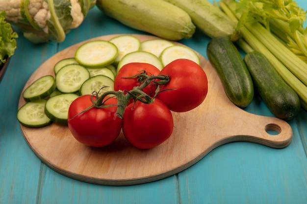 Bovenaanzicht van verse en gezonde groenten zoals tomaten, gehakte komkommers en courgettes op een houten keukenbord met selderij, bloemkool, komkommers en courgettes geïsoleerd op een blauwe houten ondergrond