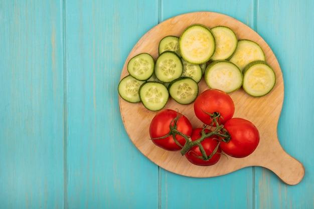 Bovenaanzicht van verse en gezonde groenten zoals tomaten, gehakte komkommers en courgettes op een houten keukenbord op een blauwe houten muur met kopie ruimte