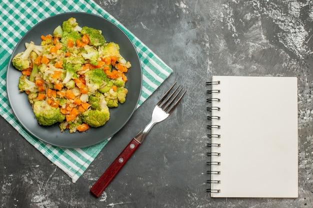 Bovenaanzicht van verse en gezonde groentesalade op groene gestripte handdoek en notitieboekje op grijze tafel