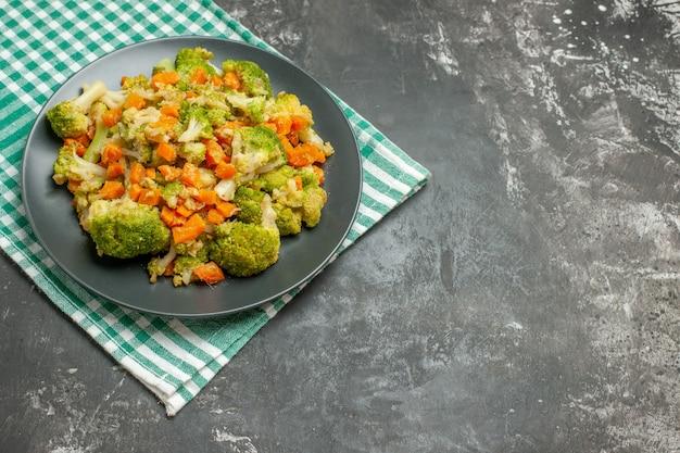 Bovenaanzicht van verse en gezonde groentesalade op groene gestripte handdoek op grijze tafel