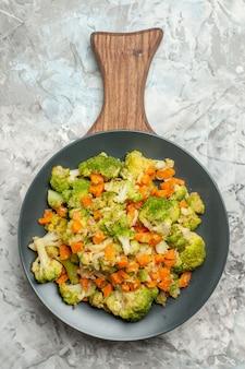 Bovenaanzicht van verse en gezonde groentesalade op houten snijplank op witte achtergrond