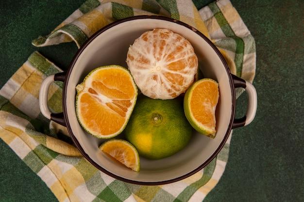 Bovenaanzicht van verse en gezonde mandarijnen op een kom op een gecontroleerde doek