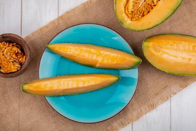 Bovenaanzicht van verse en heerlijke meloenplakken op blauw bord op zakdoek op wit
