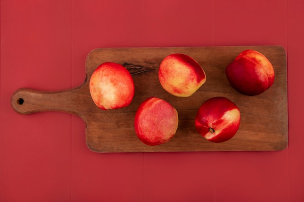 Bovenaanzicht van verse en heerlijke perziken geïsoleerd op een houten keukenbord op een rode achtergrond