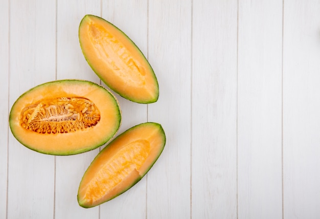 Bovenaanzicht van verse en heerlijke plakjes meloen meloen op wit hout met kopie ruimte
