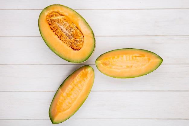 Bovenaanzicht van verse en heerlijke plakjes meloen meloen op wit hout