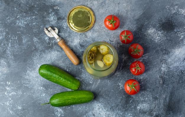 Bovenaanzicht van verse en ingemaakte groenten. geopende augurkpot met verse tomaat en komkommer
